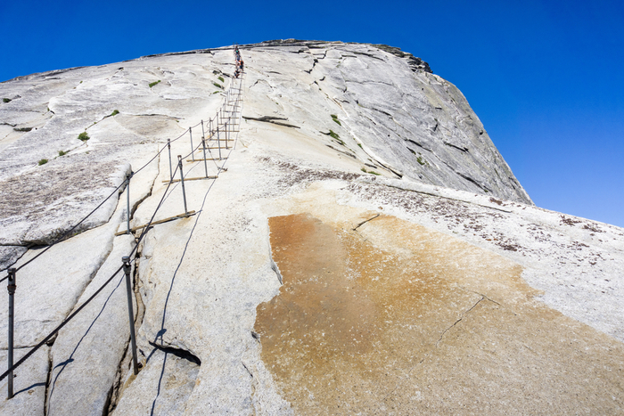 Hikers need the assistance of steel cables to get to the top of Half Dome