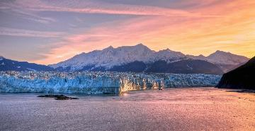 colorful sunset with a glacier and mountains in glacier bay national park